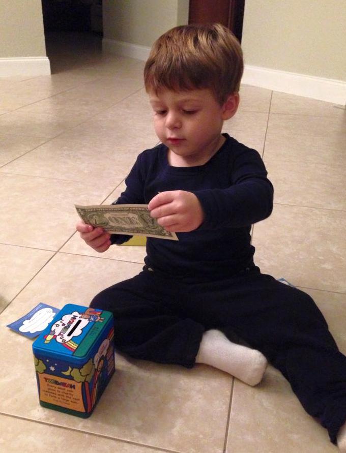 Child putting money in tzedakah box