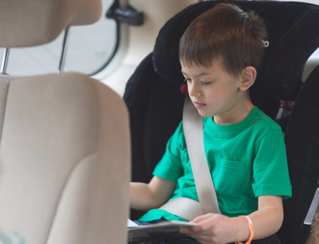 Little boy reading during road trip