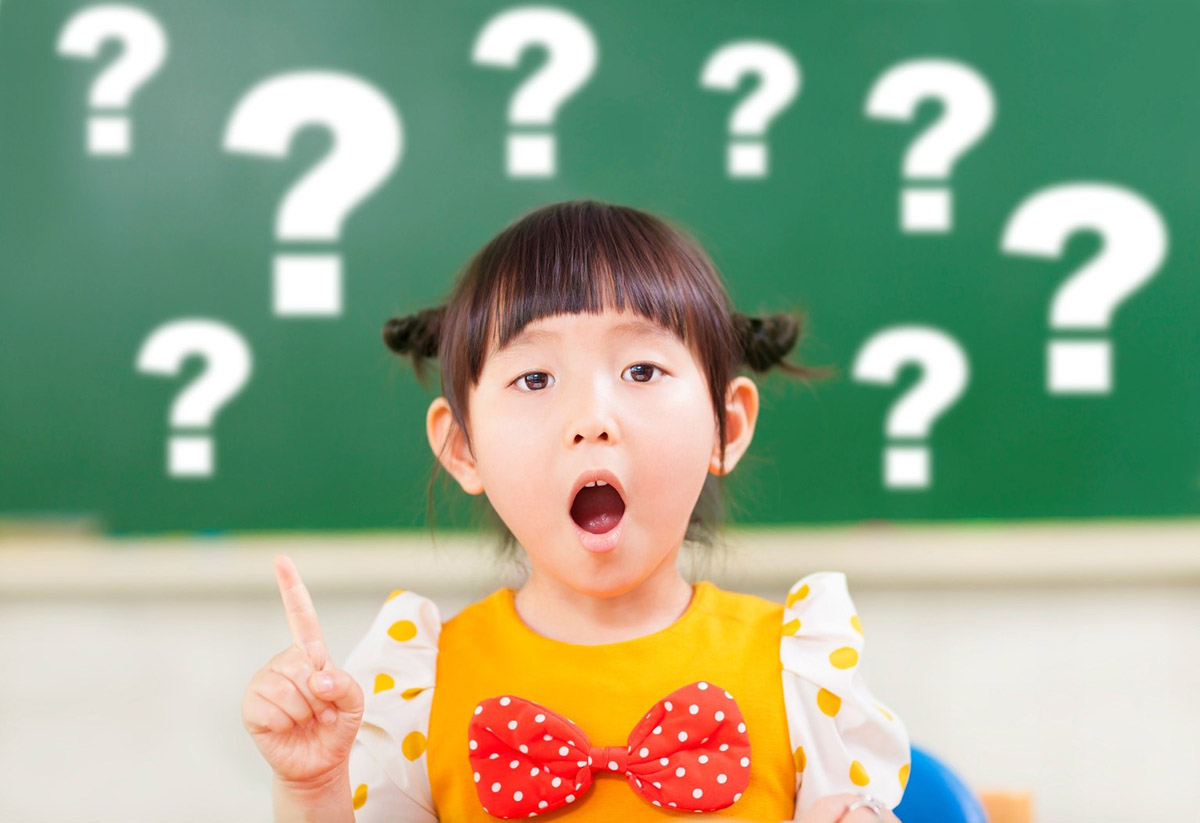 girl standing in front of a chalkboard with question marks on it