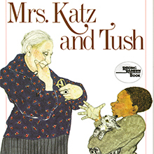 Book cover art for Mrs. Katz and Tush. A young boy holding a kitten conversing with a woman, Mrs. Katz.