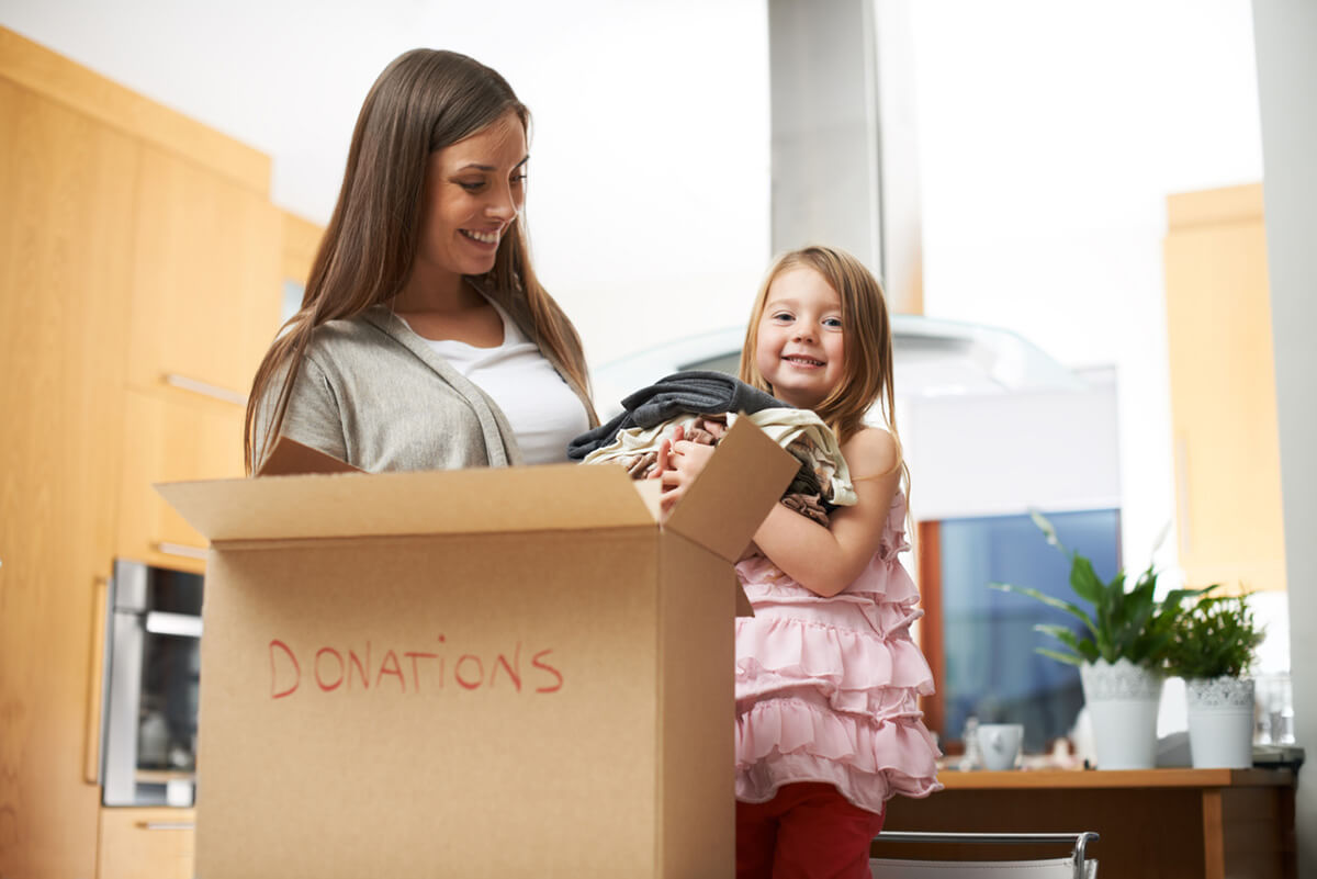 Mom and child cleaning out closet to donate clothes