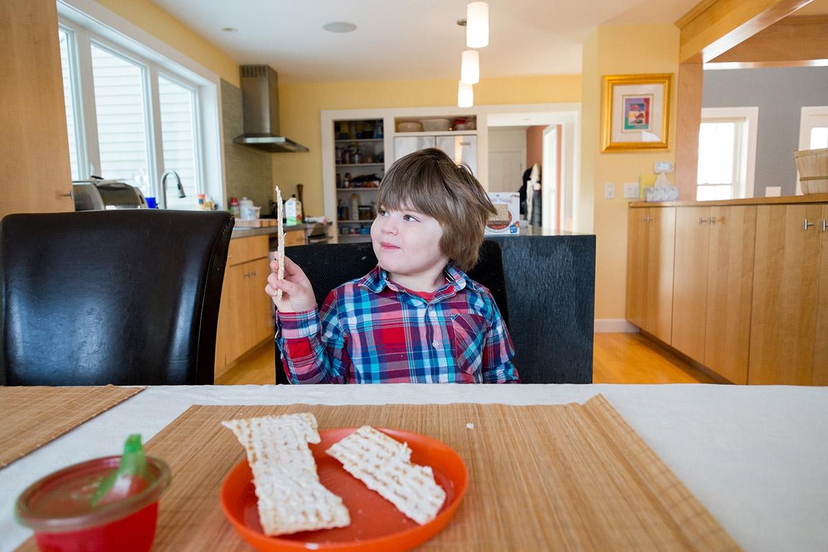 Boy holding up piece of matzah