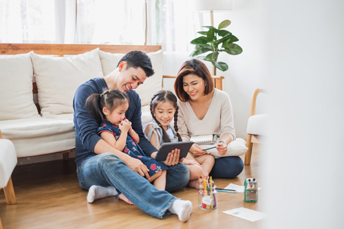 A family of four sitting down with an Ipad and a notepad