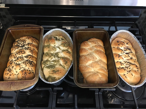 four loaves of challah in bread pans
