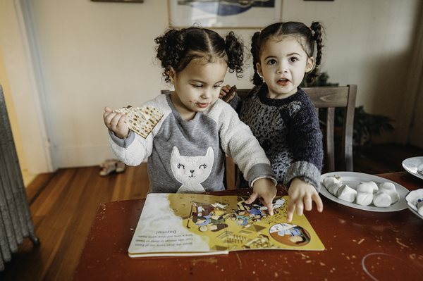 Twin sisters enjoy a snack while reading a PJ Library book