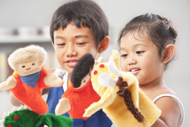 Sibling playing with puppets