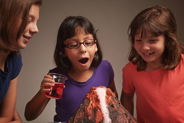 Girls watching homemade volcano erupt