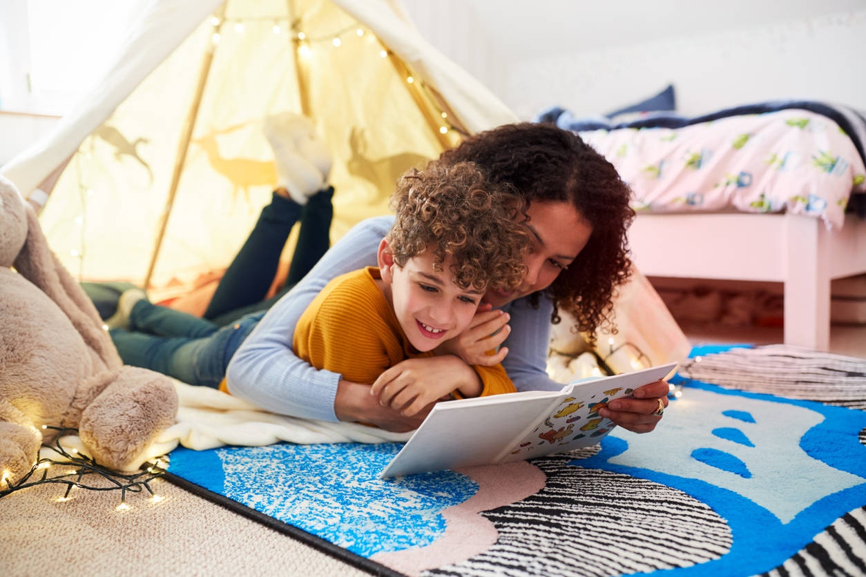 Mom and son reading together in a homemade fort