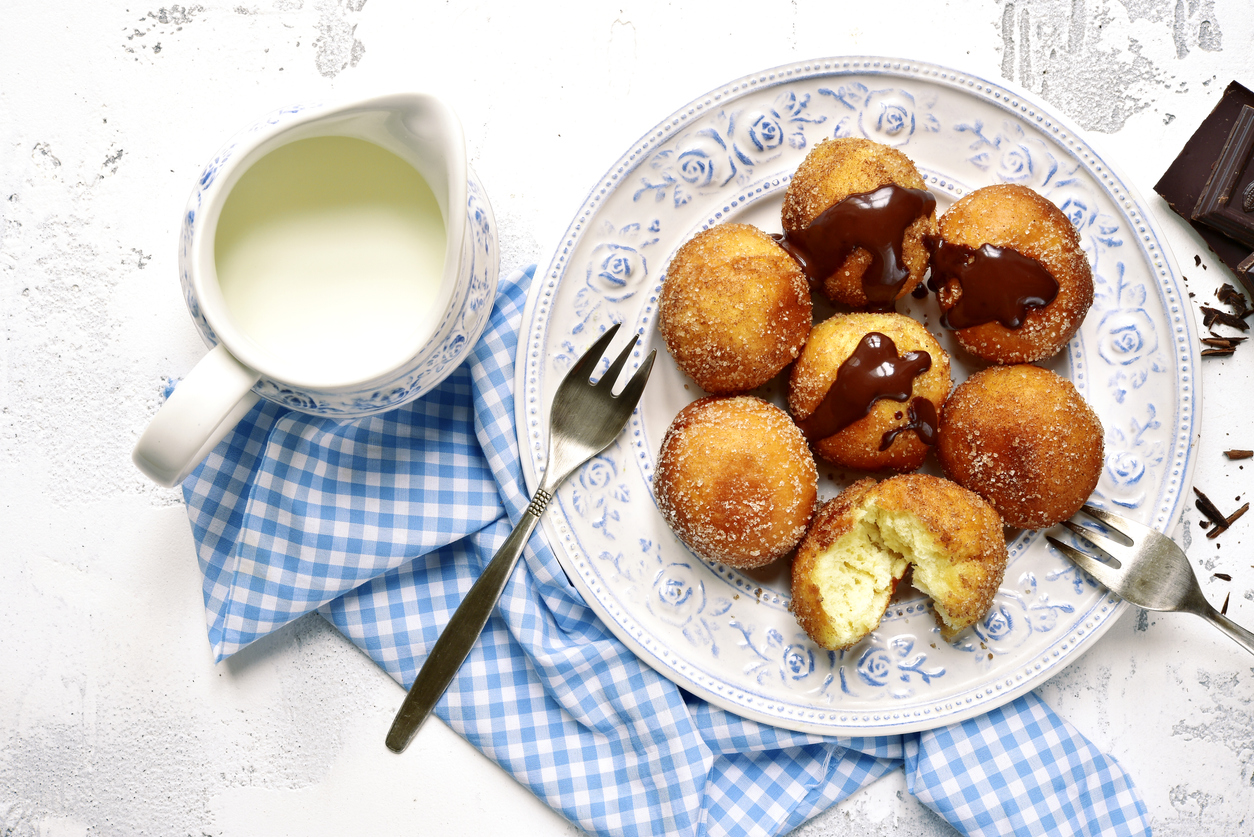 a plate of bimuelos, fried dough balls, with chocolate hazelnut spread and a pitcher of cream