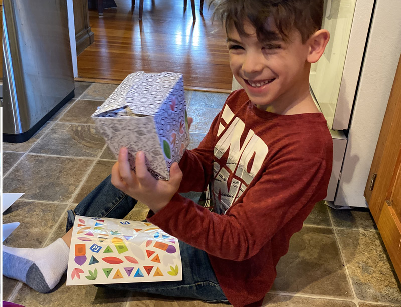 boy sitting on kitchen floor decorating mishloach manot for Purim