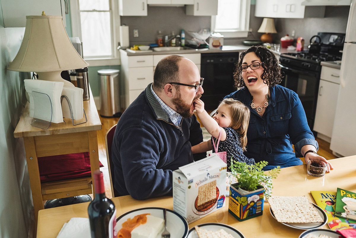 girl feeds matzah to dad as mom looks on