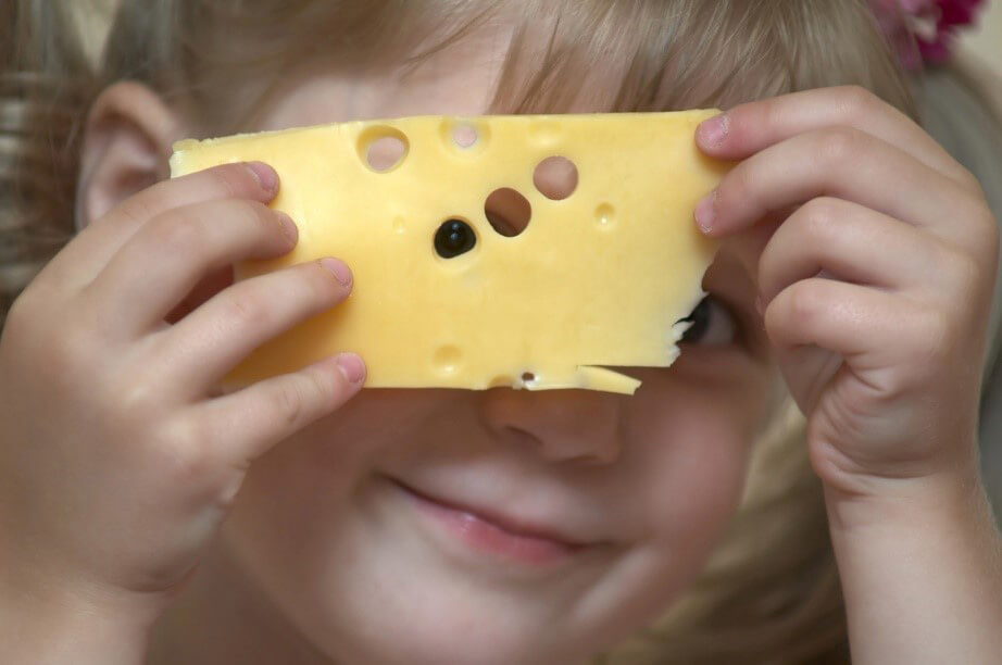Child holds up piece of swiss cheese and looks through it