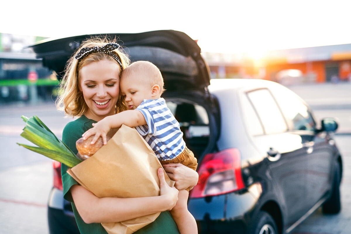 Woman and baby hold paper grocery bag in front of a car