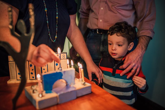 Family lighting the menorah together
