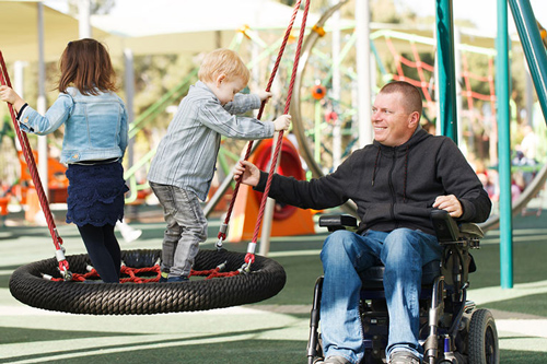 A man in a wheelchair assists children playing on a tire swing at a playground.