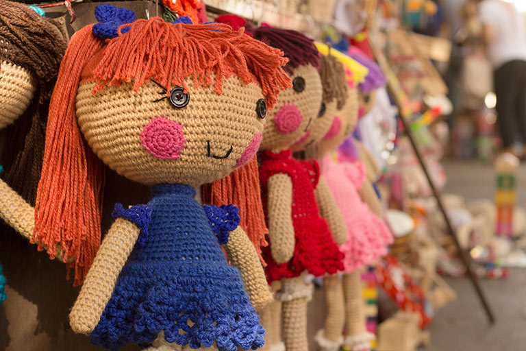 Hand knitted dolls on a sales display.
