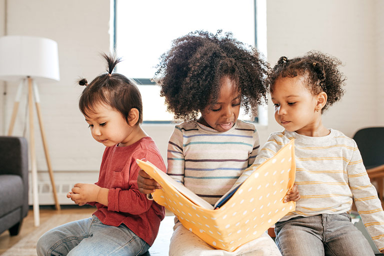 Three young children looking at a book with a yellow Polka Dot cover.