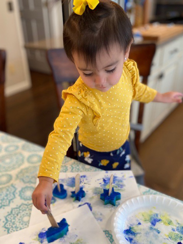 A little girl makes Hanukkah art wiht a homemade stamp