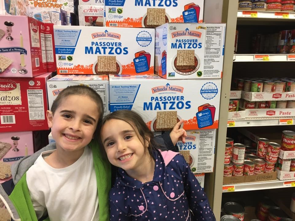 Boy and girl standing in front of PJ Library Yehuda Matzah boxes