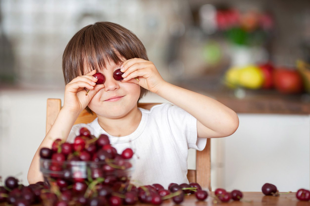 Child holding cherries up to eyes